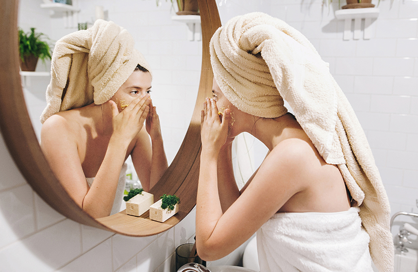 Lady placing cosmetics on her face with a towel wrapped around her head and body.