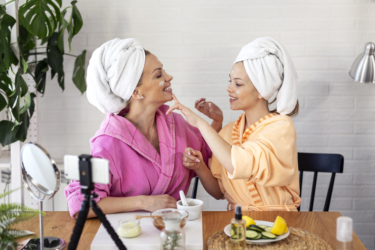 Mother and her daughter preparing natural mask with cream and honey and record video for on line blog, wondering about Hereditary Skin Conditions.