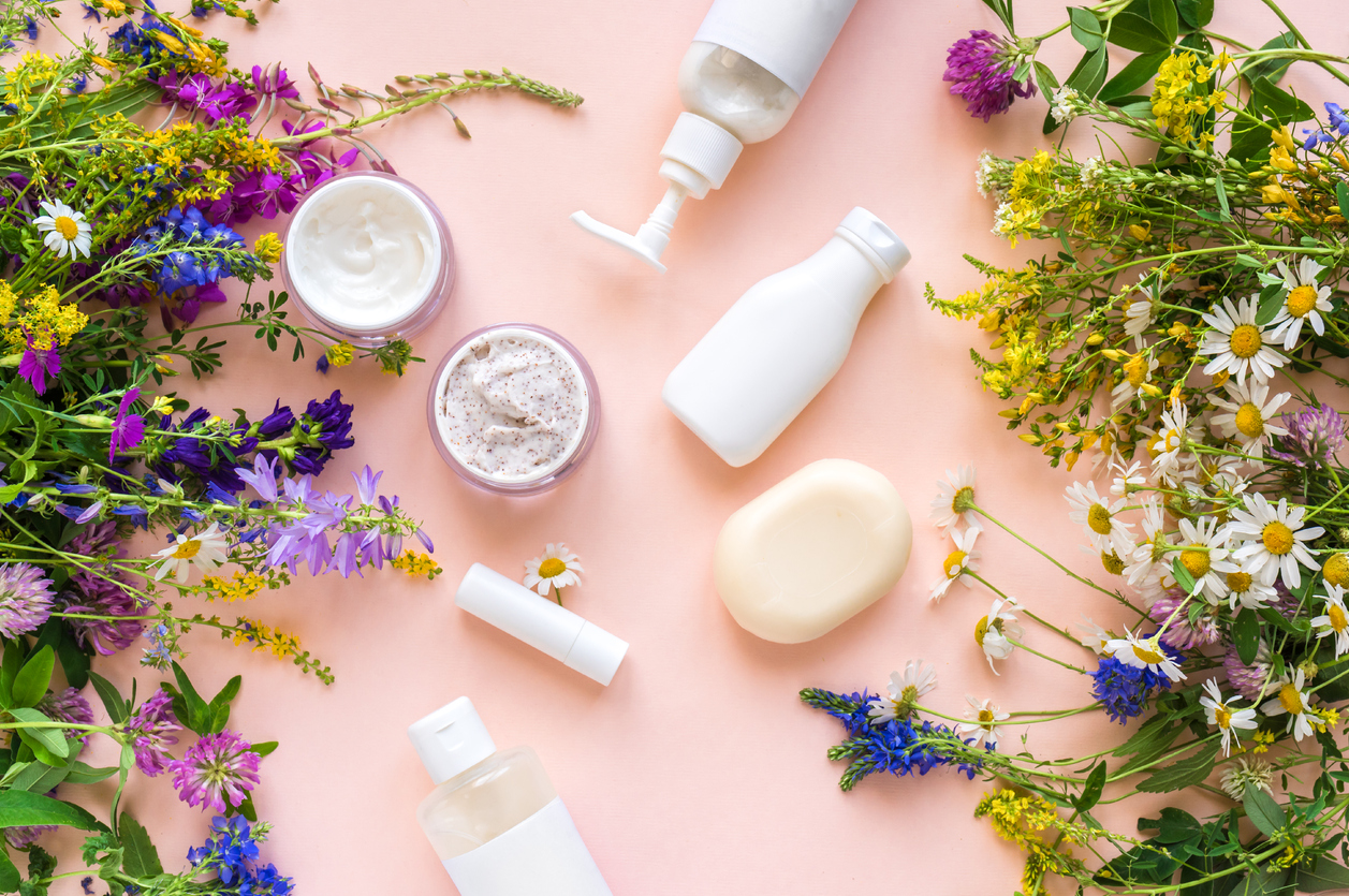 "Eco friendly skincare. Natural cosmetics and organic herbs and flowers on pink background, top view, flat lay. Bio research and healthy lifestyle concept, highlighting Are ""Organic"" Skincare Products Really Better?"