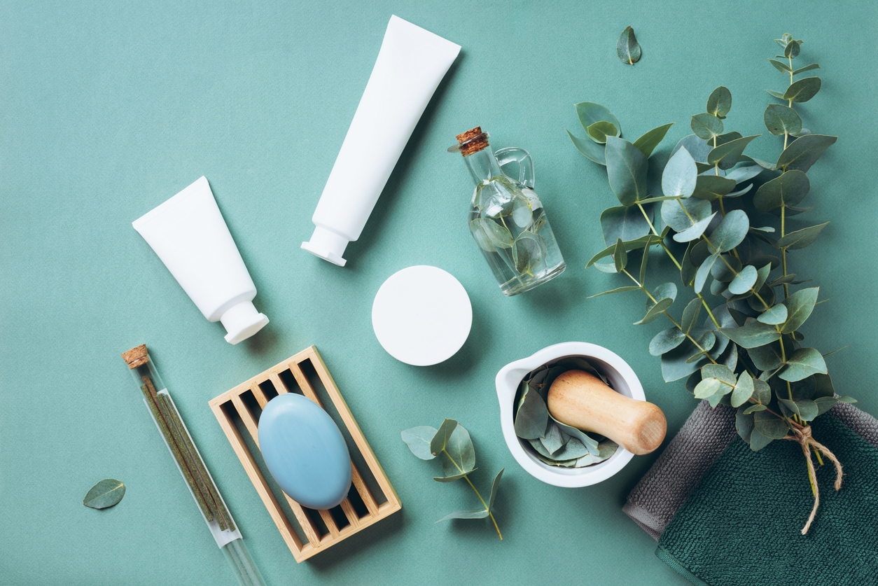White cosmetic bottles, eucalyptus flowers, towels, soap on green background. Top view, flat lay. Natural organic beauty product concept. Spa, skin care, body treatment, highlighting the history of skincare.
