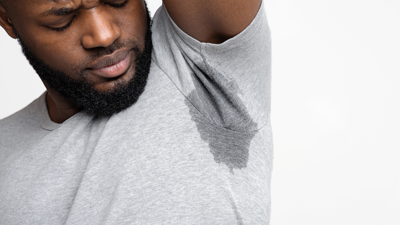 Young Black man smelling his wet armpit, close up, empty space, wondering if he has hyperhidrosis.